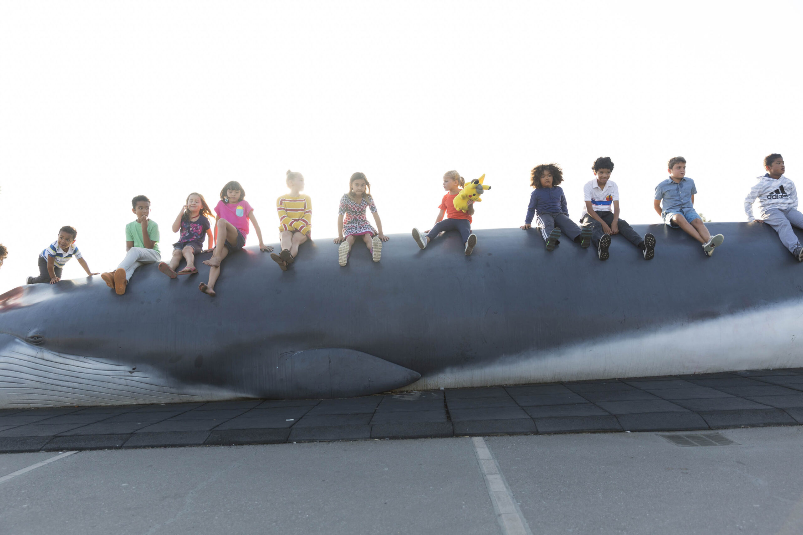 Children sitting on Pheena the Fin Whale on the plaza at The Lawrence