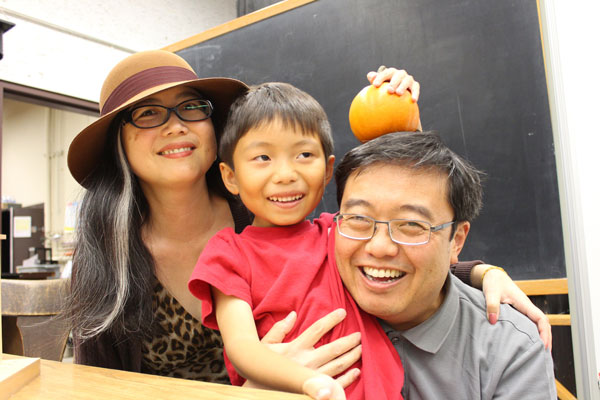 A family smiling together and the child is holding a pumpkin