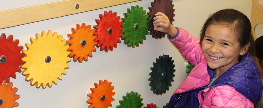 A young person turning gears on an exhibit