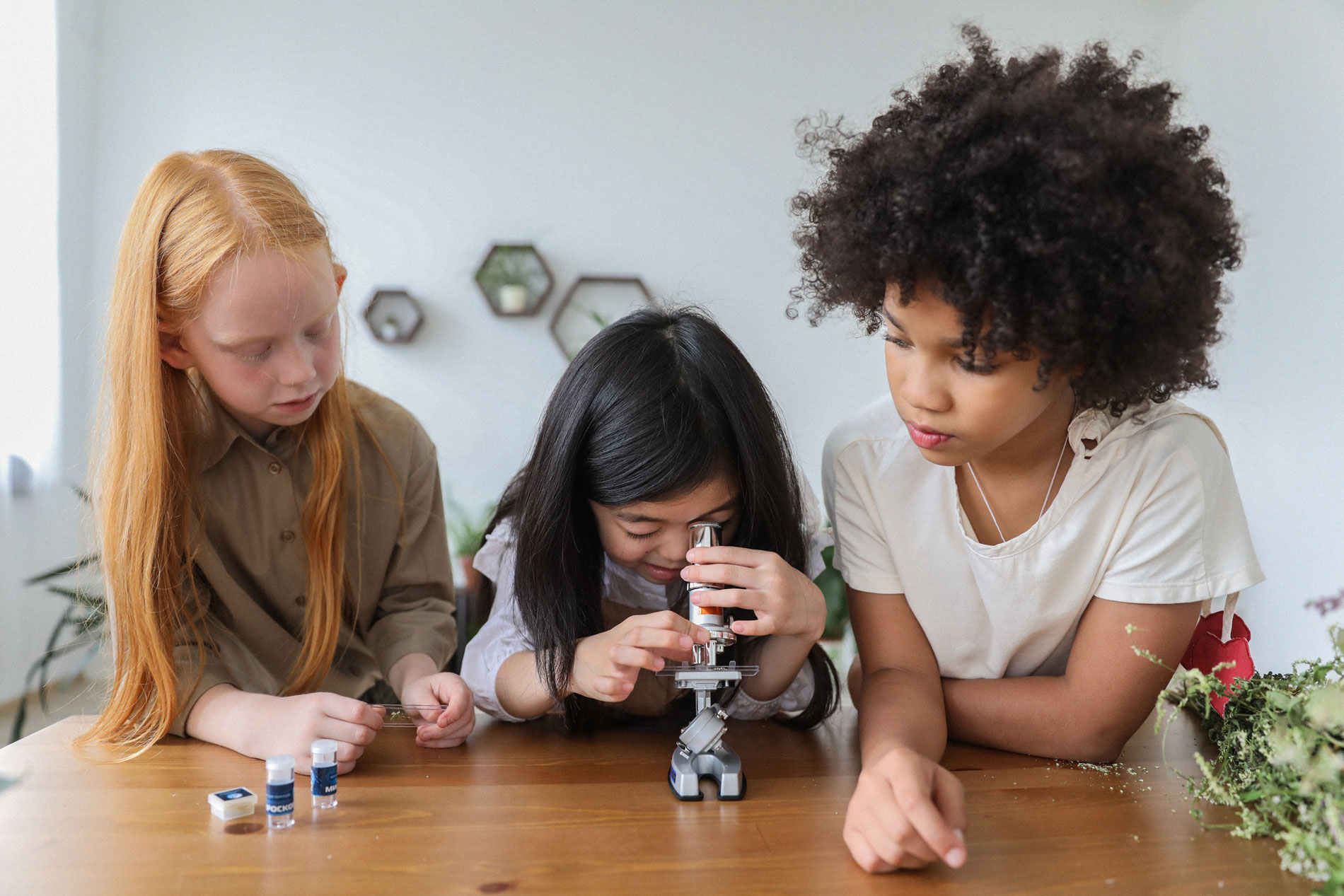 A child looking through a microscope with two children looking on