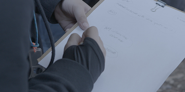 A student writes on a clipboard while conducting an outdoor science experiment in a schoolyard.